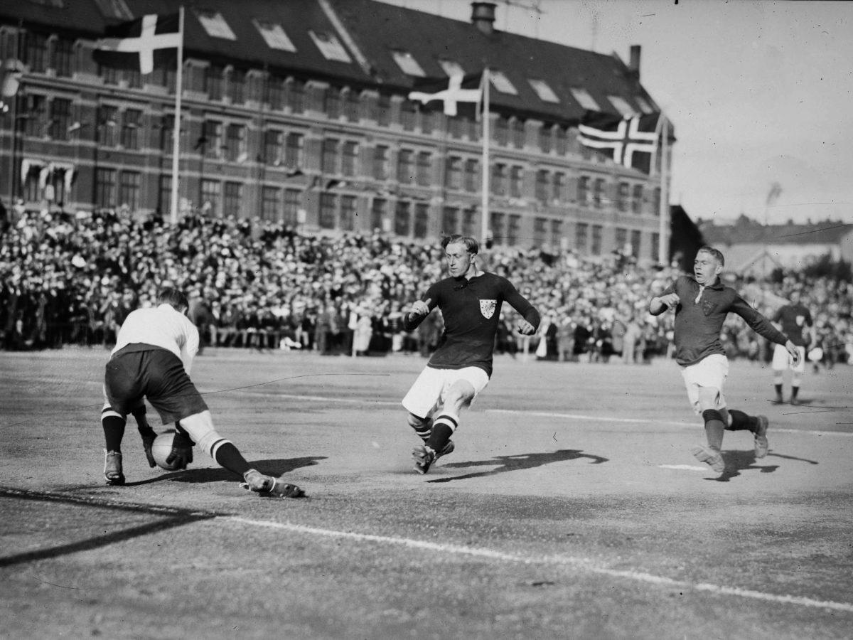 Fotball. Keeper griper ballen langs bakken. To angrepsspillere løper mot ham. Norske og danske flagg.