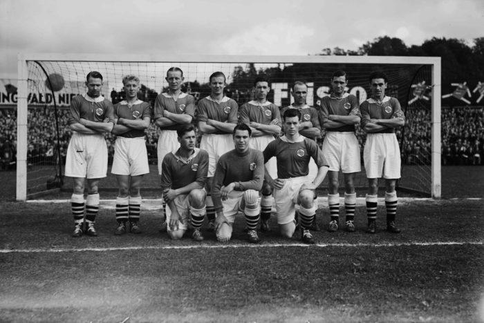 Det norske herelandslaget i fotball. Lagbilde. 30-tallet. Tre sitter på huk foran, resten står bak foran mål.