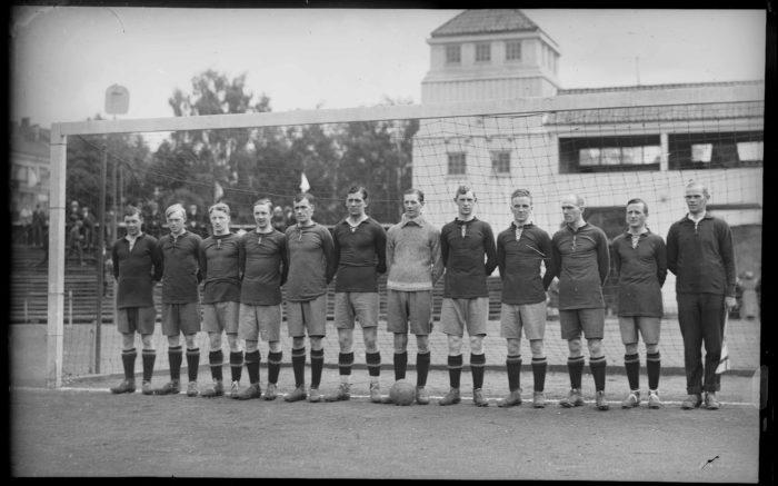 12 menn oppstilt foran fotballmål.
