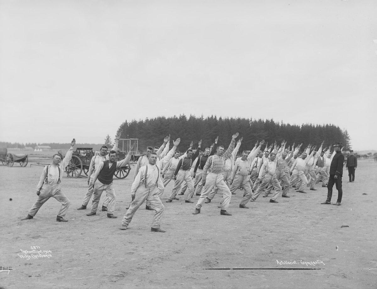 Str gruppe menn løfter venstre arm i været, bøy i venstre ben. Hest og kjerre i bakgrunnen, uniformert instruktør til høyre.