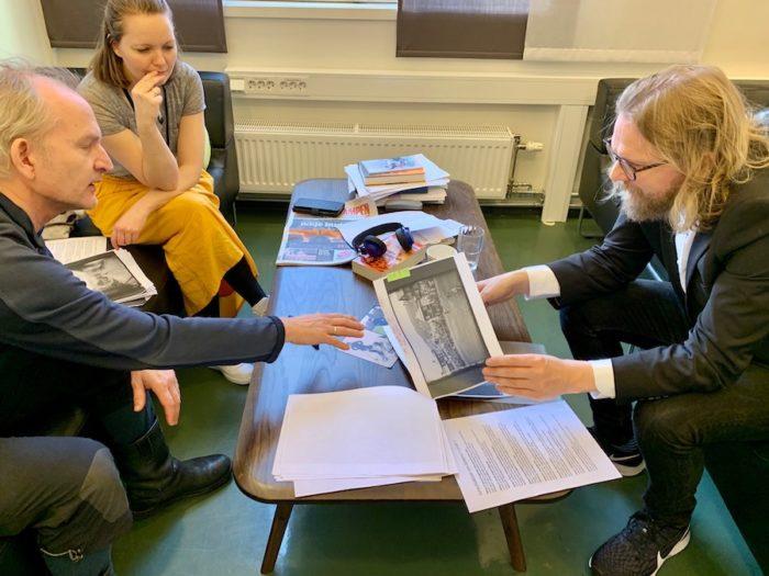 Tre personer i et møte, diskuterer bilder