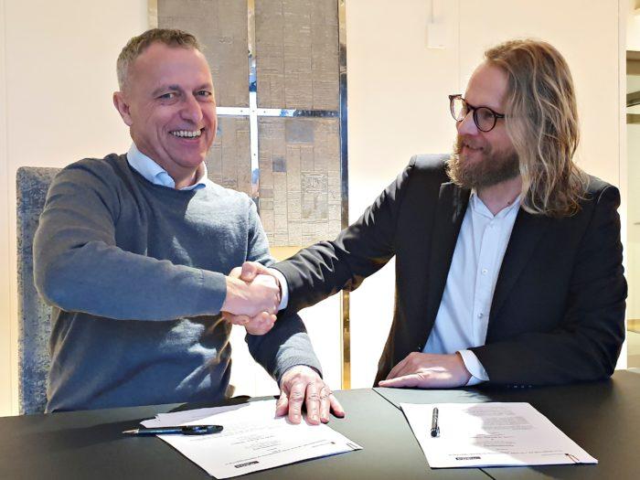 To menn som sitter med dokumenter og penner på bordet foran seg gir hverandre et håndtrykk