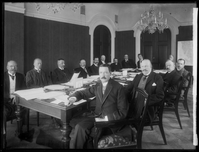 Svart-hvitt. 14 menn rundt et bord.