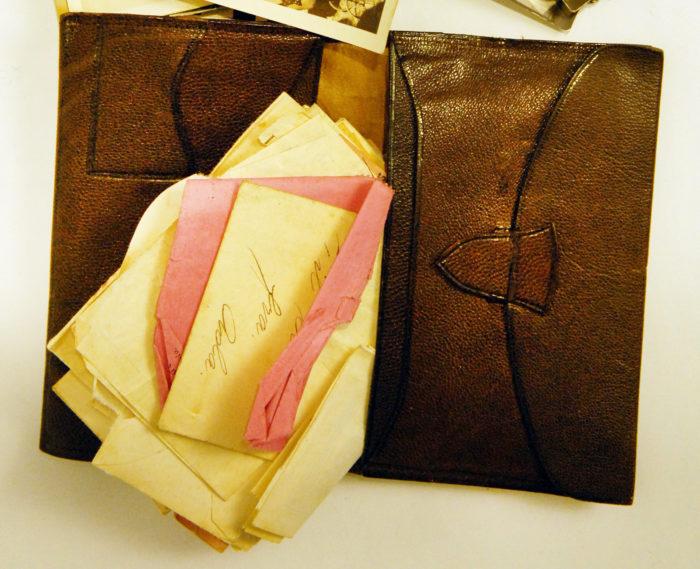 Brun skinnlommebok med gule og rosa kvitteringer.