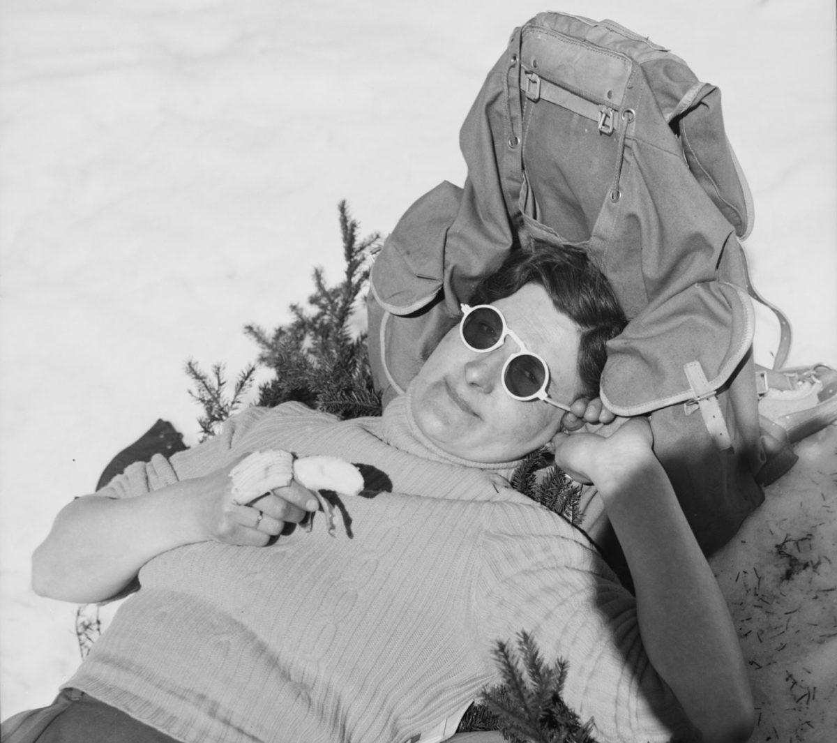 Kvinne med solbriller ligger i snøen, lener hodet mot sekk, spiser banan.