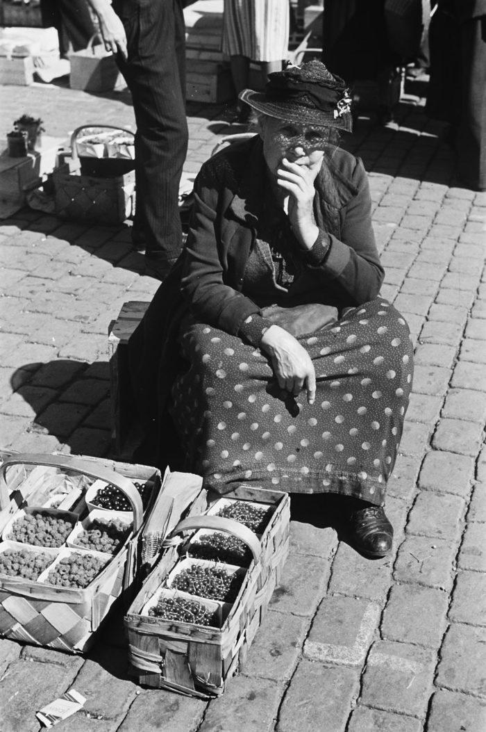 Kvinne i hatt sitter på en kasse på bakken, kurver med bær foran seg.