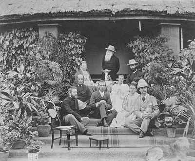 Oppstilt bilde i trapp foran hus, seks menn og tre kvinner.