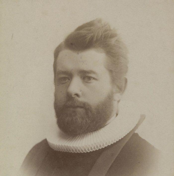 Portrett, fra siden. Mann med skjegg iført prestedrakt.