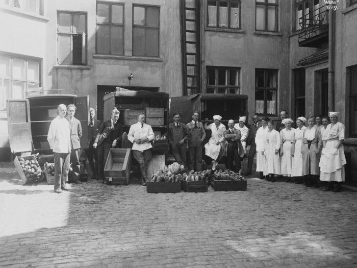 bakere oppstilt utenfor en bygning med kasser med brød.