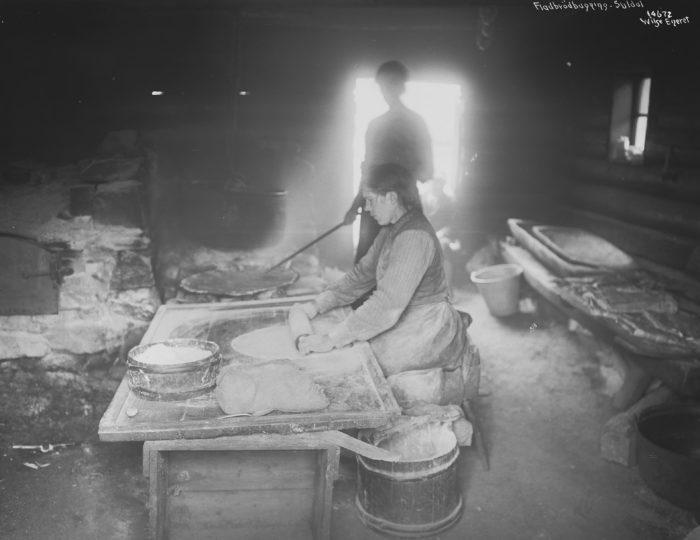 Bakehus, kvinne kjevler ut et flatbrød foran en bakerovn.
