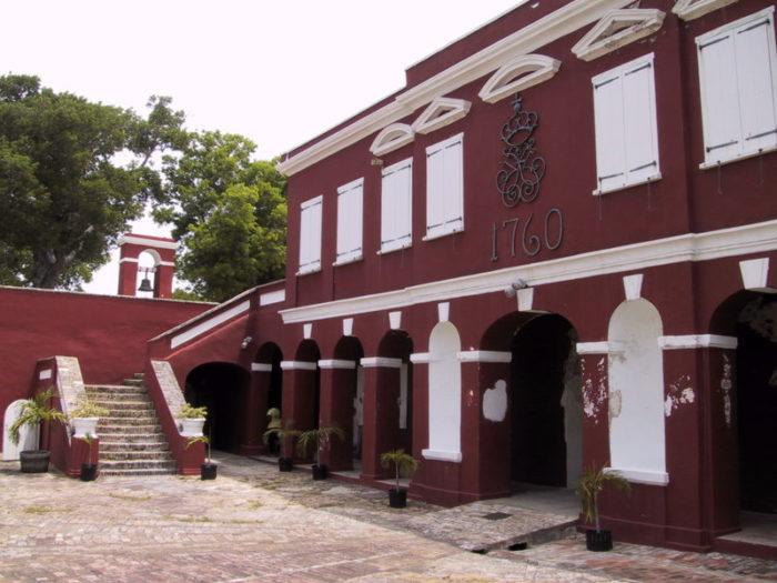 Rød bygning med hvitmalte karmer med påskriften 1760 over inngangsportalen.