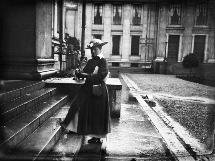 Kvinne med hatt og hansker på steintrapp