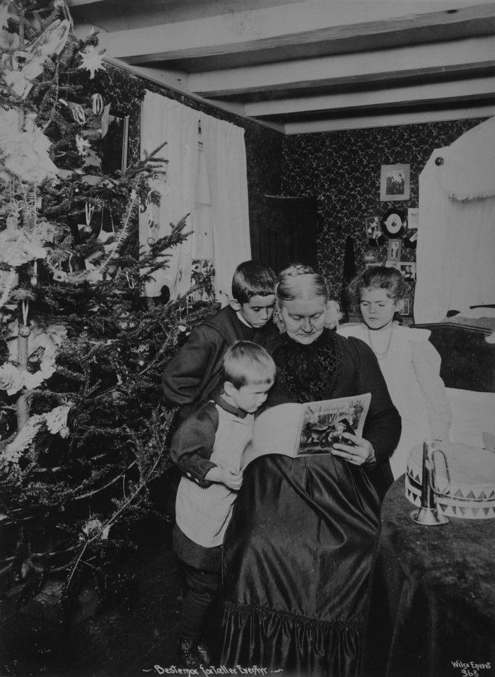 Juletre, eldre kvinne leser for tre små barn
