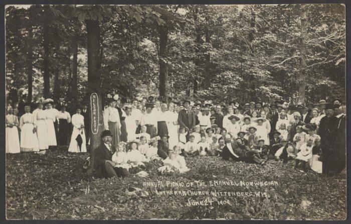 Gruppebilde, 60-70 mennesker, pent kledd, piknik i skogen.