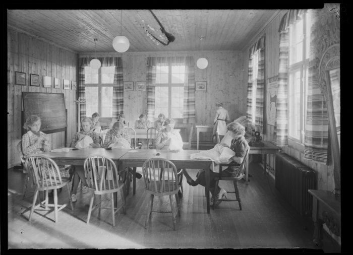 Kvinner med sytøy rundt bord.