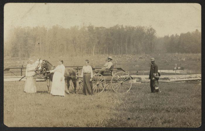 Hest og kjerre, kvinner og menn på åpen gresslette.