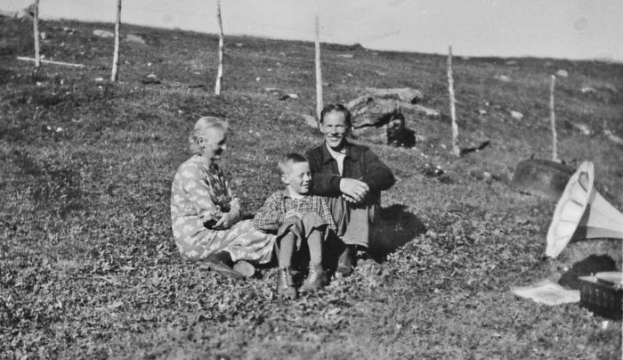 Kvinne, mann og gutt sittende utendørs med en grammofonspiller