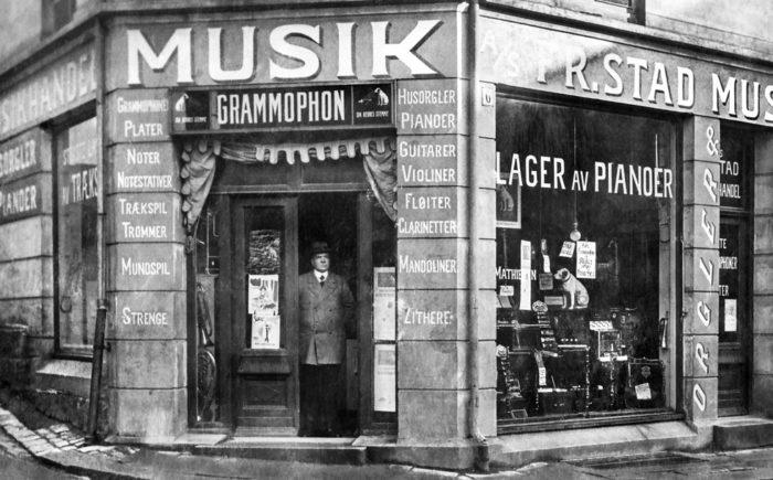 Bilde av butikkfasade med tekst Musikk m.m. Stående mann i døråpningen.
