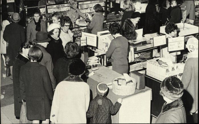 Bilde skrått ovenfra av kassene ved utgangen på stort kjøpesenter med mange besøkende.
