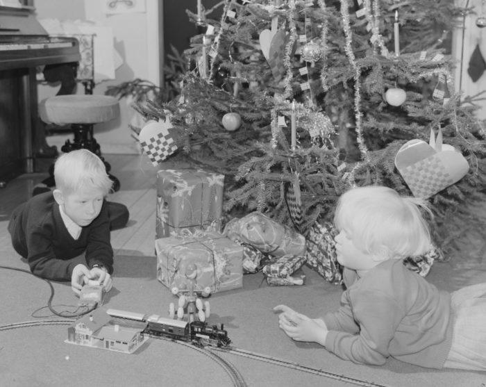 To barn foran juletre som leker med modelltog