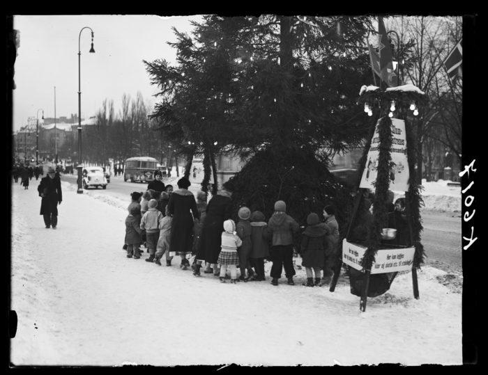 Juletre, barn med ryggen til og ansiktet mot treet.
