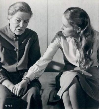 To kvinner sitter på en seng og snakker sammen.