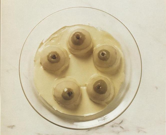 Fem halvveis skrelte pærer i en bolle med saus, sett ovenfra