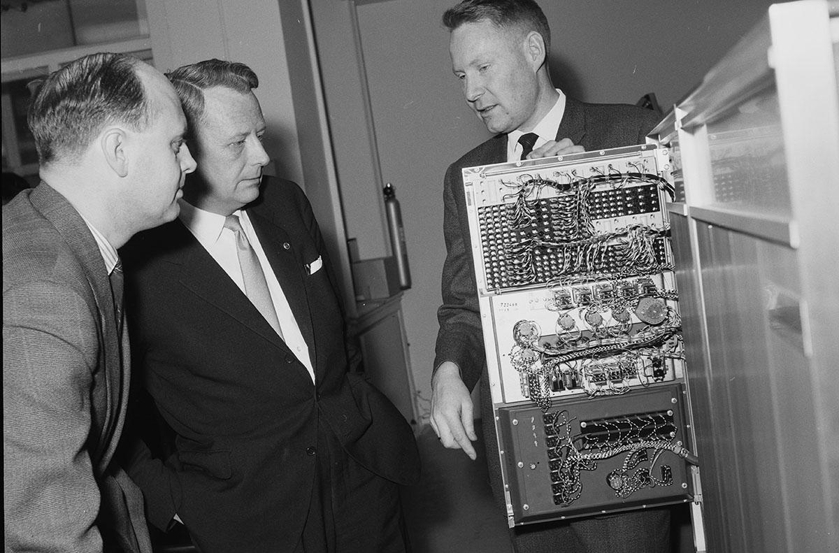 Svart-hvitt foto fra 1963 av tre menn i dress og slips står rundt et åpent skap til en stordatamaskin. Mange ledninger på et panel.