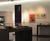 oversiktsbilde fra utstillingen - rom med monter og plakater